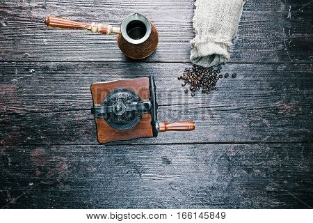 Sack of coffee beans with pot and hand grinder on the table. Overhead view