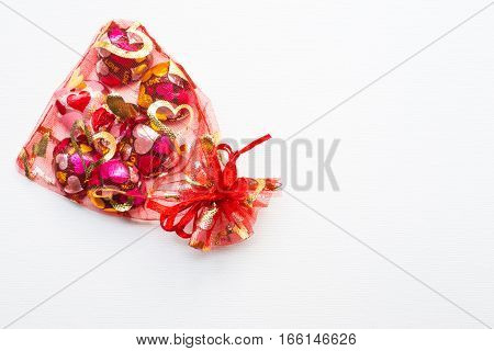 Close up of Chocolate heart-shaped in red bag on white background
