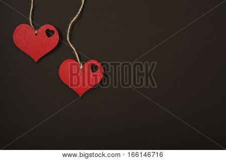 red hearts on a rope on a black background