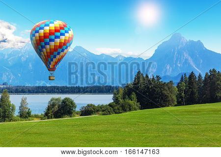 Scenic summer landscape with colorful hot air balloon flying above Alps mountains lake and green field or meadow and forest in Bavaria Germany Central Europe