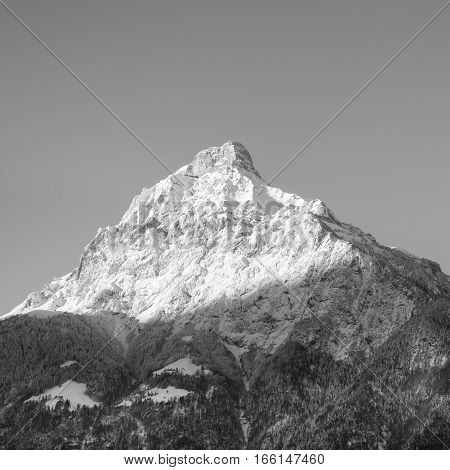 Sun rises and illuminates the tops of the mountains. Winter landscape snow in the mountains. Moon is visible above the mountains. Black and White.