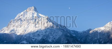 Sun rises and illuminates the tops of the mountains. Winter landscape snow in the mountains. Moon is visible above the mountains.