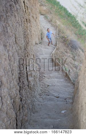 boy climbs the stairs to the mountain