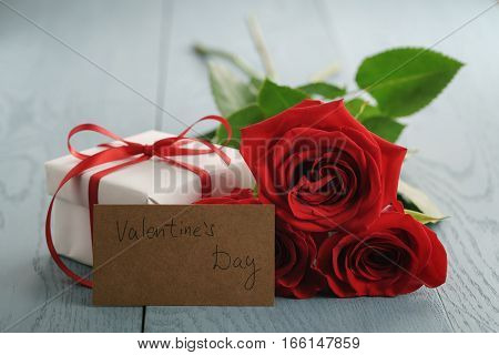 three red roses on blue wood table with gift and valentines day paper card, shallow focus