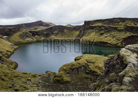 Laki crater lake Tjarnargigur on Iceland with green grass