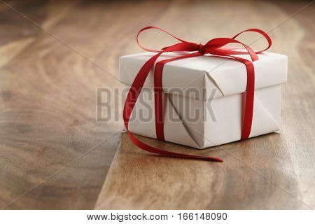 white paper gift box with thin red ribbon bow on old wood table, with copy space