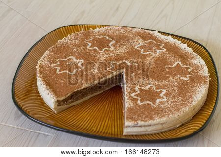 Christmas coffee cake with creamy souffle decorated star on beige wood.
