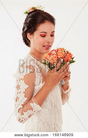 A gorgeous young bride smelling her bouquet