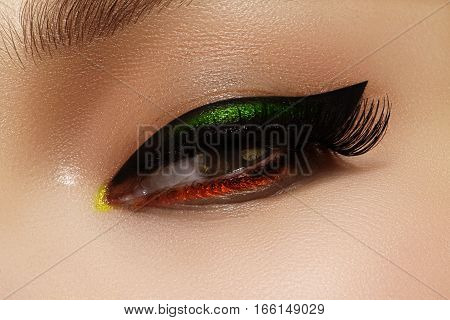 Close-up photo of female eyes with black eye liner. Fashion makeup with perfect arrows shape. Retro style and chic evening make-up. Cosmetics and make up.