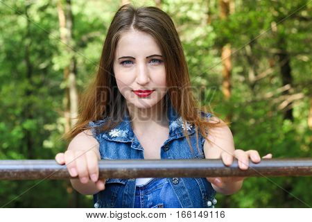 A young woman holds on to the railing, amid forest.