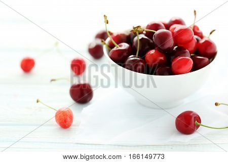 Ripe Cherries In Bowl On A White Wooden Table