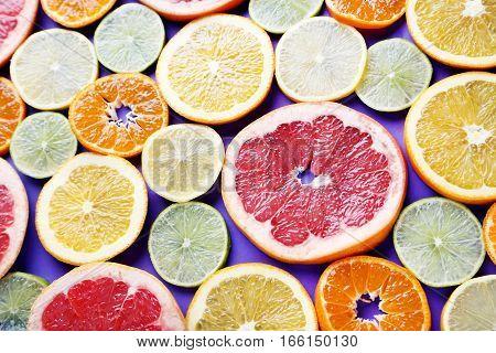 Citrus fruits on a purple background, close up
