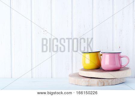 Pink and yellow mug on white wall paneling background