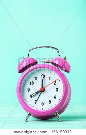 Pink Alarm Clock On A Green Background
