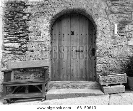 Black and white image of a classic old wooden door in the Pyrenees in Spain with a bench and flower pot either side.