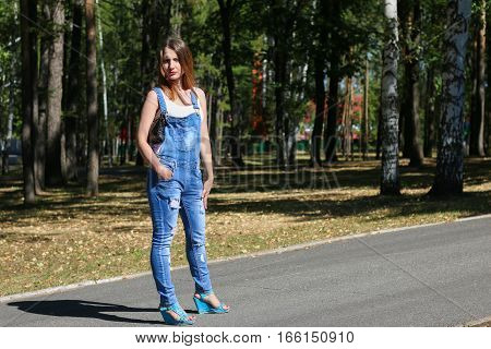 Woman in overalls standing in the park.