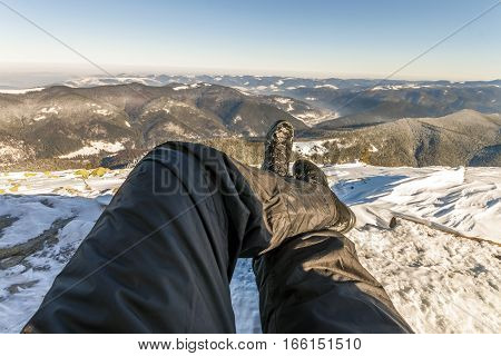 Mens legs in winter shoes against panorama over the Carpathian mountains.