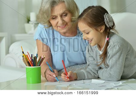 Portrait of a happy grandmother with granddaughter drawing together