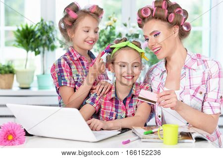 portrait of happy  Mother and little daughters in hair curlers with laptop  at home