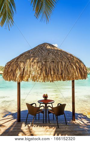 Two chairs and coffee table under a thatched parasol on a sand beach with a view on the lagoon