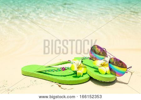 Tropical vacation concept--Green flip-flops and sunglasses on a sandy ocean beach with small fish in the water