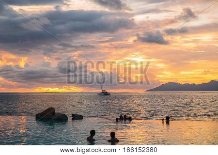 Silhouettes of people in swimming pool celebrating gorges sunset and beautiful evening sea