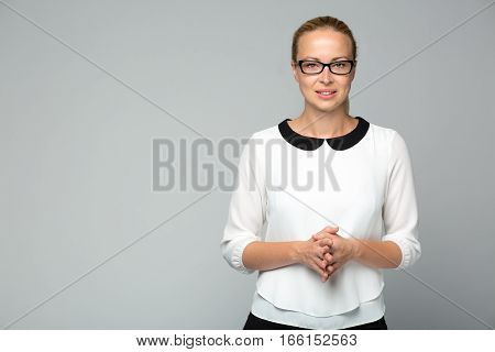 Portrait of beautiful smart cheerful young businesswoman wearin black eyeglasses, standing with arms steeple against gray background. Copy space on left.