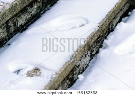 Closeup footprints in the snow on a concrete staircase in winter.