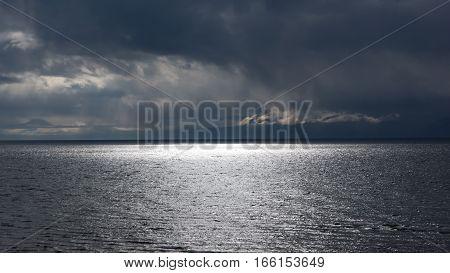 Sunbeams over the water in the rain on Lake Baikal