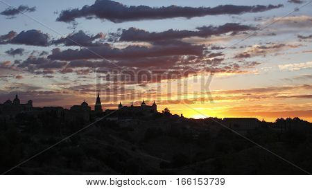 Dawn in Toledo, Castilla La Mancha,Spain, backlit, yellow background and black silhouette sky over the city silhouette view of the main medieval monuments