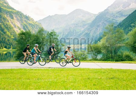 family of four cycling by the vilsalpsee in austria