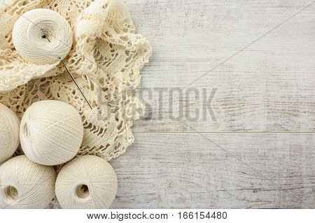 crochet tablecloth crochet hooks and balls of cotton thread on a white wooden table. top view copy space