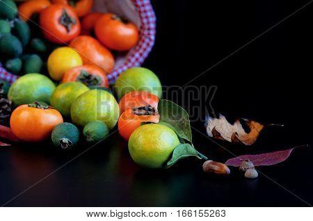 Fruits in basket: persimmons, lemons, pineapple guava with autumn leaves. Lemon Fresh fruit Persimmon Feijoa Fern Wicker basket Dark background Hands
