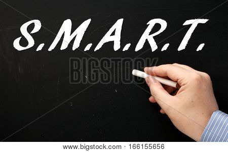 Male hand in a business suit writing the word SMART on a blackboard as a reminder to plan your goals in a specific,measurable,achievable,relevant and timely manner