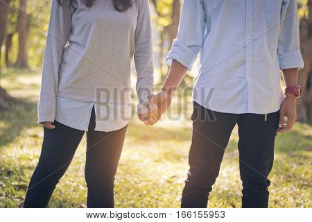 Young couple holding hands in garden with sunlight valentine day.
