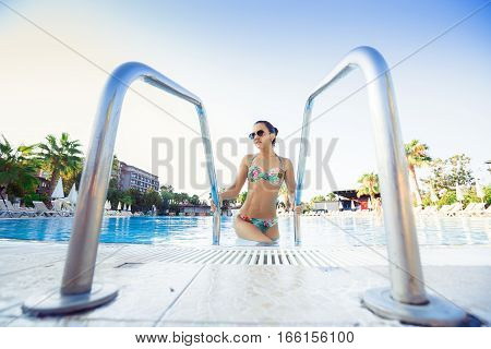 Young brunette woman coming out of the swimming pool