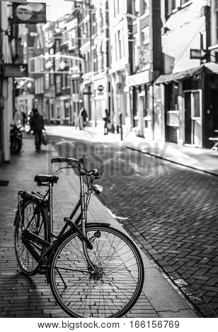 Parked in city street bicycle close-up. Black-white photo.