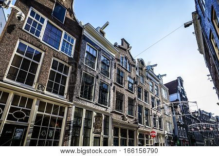 AMSTERDAM NETHERLANDS - DECEMBER 17 2017: Famous buildings and place of Amsterdam city centre at sun set time. General landscape view. December 17 2016 - Amsterdam - Netherlands.