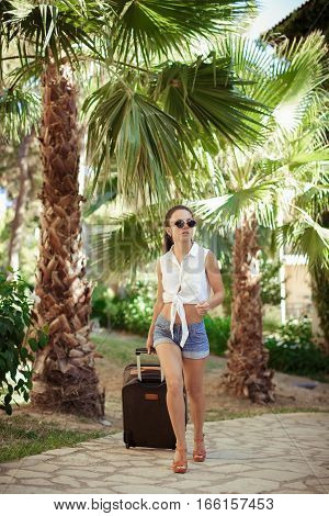 young woman in sunglasses, white shirt and shorts comes with  suitcase