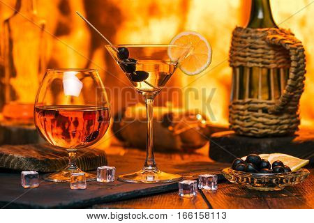 Martini glass and brandy snifter with drinks. Icecubes and olives near them. Fireplace lights on the background