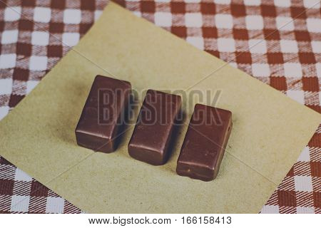 Chocolate Candy On A Piece Of Paper, A Checkered Background