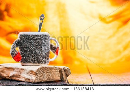 Teacup wearing sweater cozy with teaspoon inside on wood stands