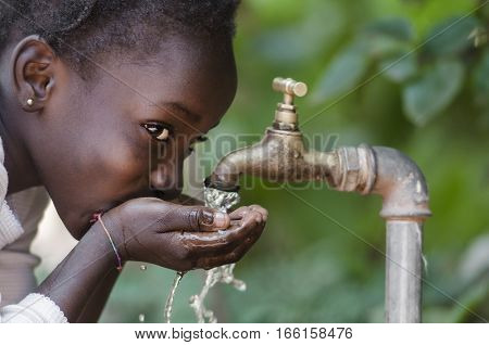 Beautiful African Child Drinking from a Tap (Water Scarcity Symbol). Young African girl drinking clean water from a tap. Water pouring from a tap in the streets of the African city Bamako Mali.