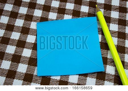 A Blue Piece Of Paper For Taking Notes With A Pencil On A Table, Close-up. Checkered Background