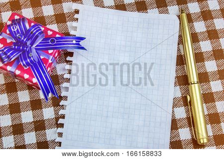 Fragmentary Piece Of Paper For Taking Notes With A Pen And The Gift On The Table, Checkered Backgrou