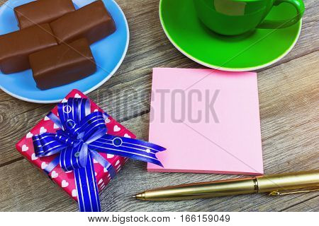 Clean Sheet Of Paper For Notes, Pen, Chocolates On A Saucer And Coffee Cup On Old Wooden Table.