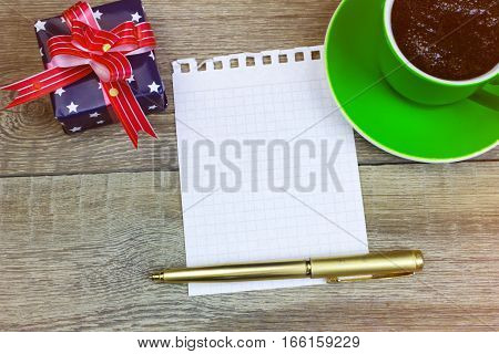 Blank Paper With Pen, Coffee Cup And The Gift On Wood Table