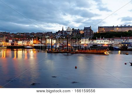 WHITBY, ENGLAND - JUNE 30, 2016: The harbor in the port of Whitby on the North Yorkshire coast at dusk. Tourism started in Whitby during the Georgian period and developed further on the arrival of the railway in 1839.
