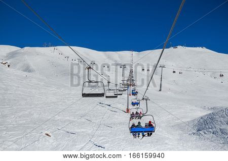 Skiers on a ski lift at winter mountain resort