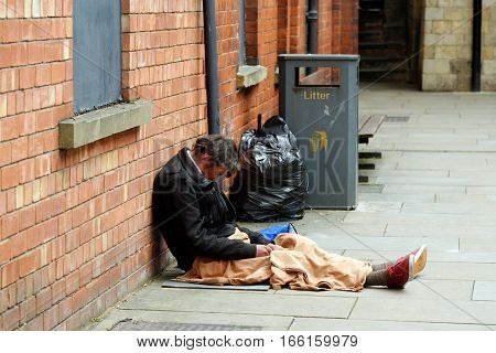 LINCOLN, UK - JULY 1, 2016: Homeless beggar sleeping on the streets of Lincoln.